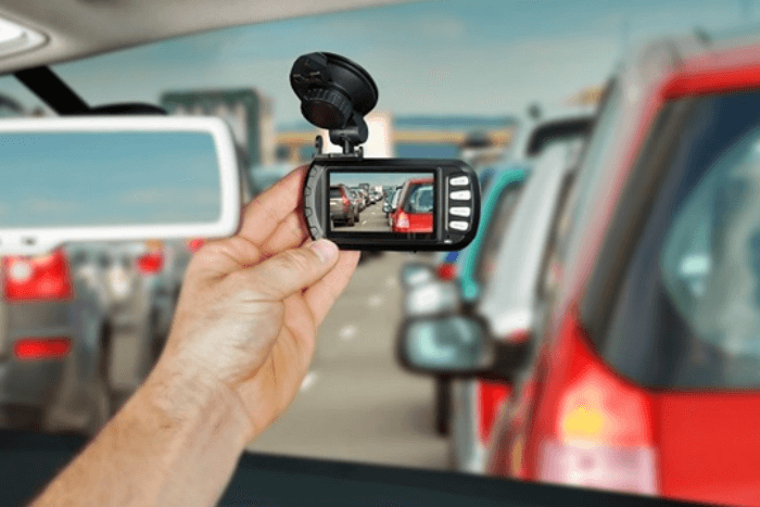 driver adjusting dashcam