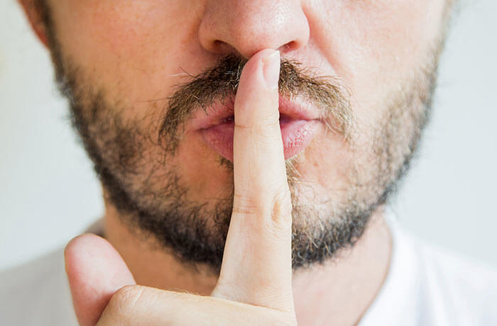 Bearded man with fingers on lips indicating quiet