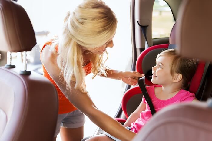 Mother putting daughter in a car seat