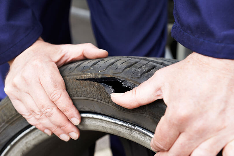 Man inspecting burst tyre
