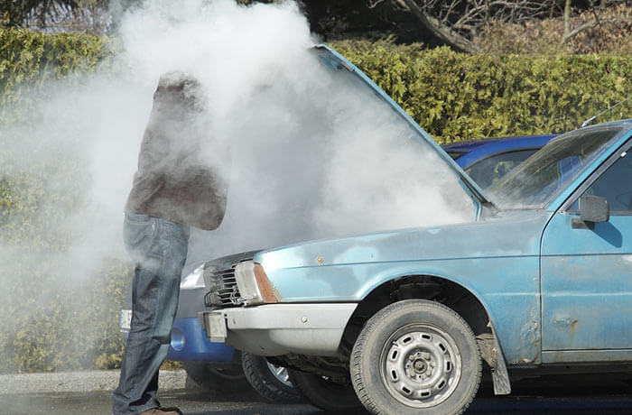 An overheated car with smoke pouring out of it