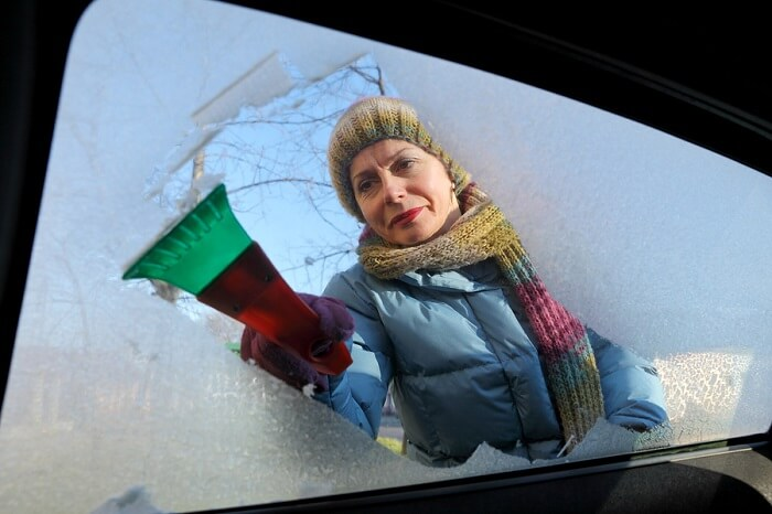 Woman scraping ice from car window