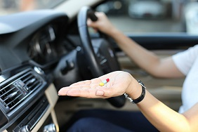 Woman taking pills in car