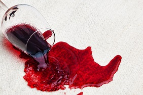 Red wine spilling on carpet