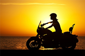 Motorbike driving into the sunset