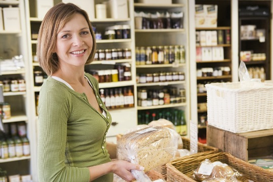 A woman holding a loaf of bread in a small deli